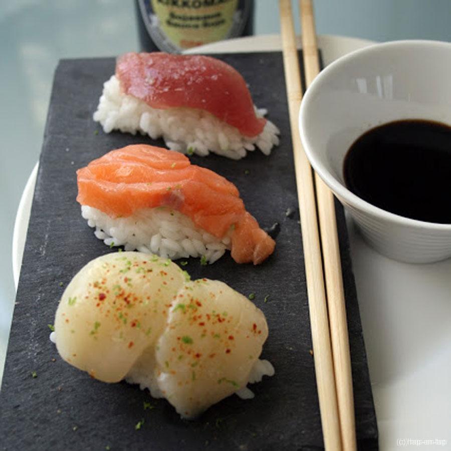 Handgerolde sushi nigiri met coquille, zalm en tonijn