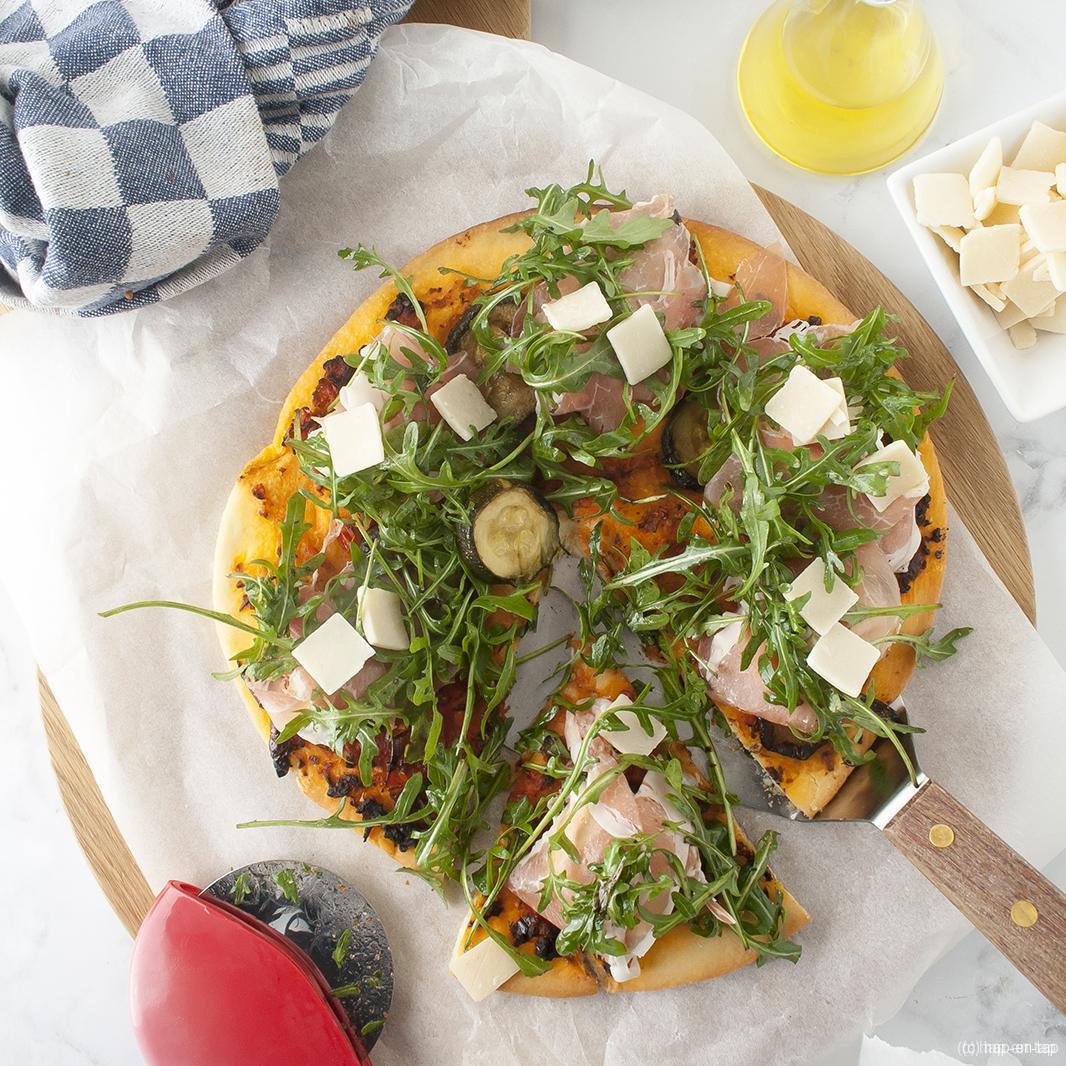 Pizza met zongedroogde tomaten, Parmaham en rucola